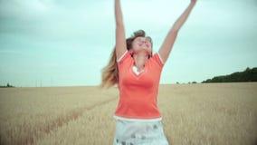 Junge Frau läuft glücklich in das Feld von Ohren entlang dem Weg in Richtung zur Sonne stock video