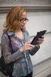 Junge Frau Latinas, die auf Tablette spricht Stockbild
