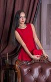 Junge Frau am Lederstuhl, der rotes Herz hält Stockfotos