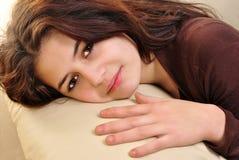 Junge Frau liegt auf einer Couch stockfotografie