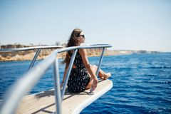 Junge Frau liegt auf einer Luxusyacht im Meer und dem Schauen zum Horizont lizenzfreie stockfotografie