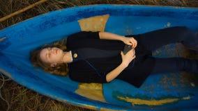 Junge Frau liegt in einem kleinen blauen Boot lizenzfreies stockbild