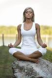 Junge Frau Lotus Yoga Position auf Felsen stockfotografie