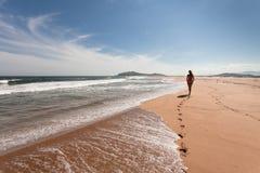 Junge Frau läuft der Abstand den leeren, wilden Strand gegen einen blauen Himmel durch, das mit gelbem Sand und Meer Fokus in Ric Stockfotografie