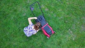 Junge Frau mäht ein grünes Gras in ihrem eigenen homeyard mit Rasenmäher 4K stock video