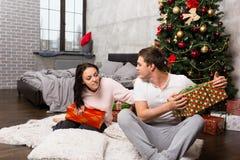 Junge Frau möchte ihr Freund ` s Geschenk sehen, aber er versteckt es w Stockbilder
