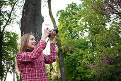 Junge Frau machen Foto von den Frühlingsblumen auf DSL-Kamera Stockfotografie