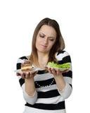 Junge Frau macht choise zwischen Kuchen und Kopfsalat Stockbild