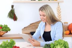 Junge Frau macht das on-line-Einkaufen durch Tablet-Computer und Kreditkarte Hausfrau gefundenes neues Rezept für herein kochen Lizenzfreie Stockfotos