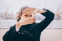 Junge Frau macht einen Rahmen von den Fingern stockfoto