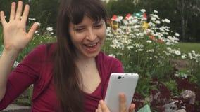 Junge Frau macht einen Videoanruf telefonisch auf einem Hintergrund von camomiles draußen stock video footage