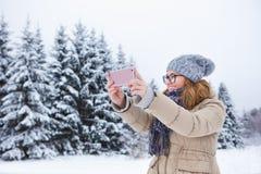 Junge Frau macht Foto auf einem Hintergrund des schneebedeckten Winterwaldes Lizenzfreie Stockfotos