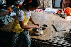 Junge Frau macht kosmetische Paste von der Grundbarke in einem kleinen Dorf nahe Bagan stockbilder