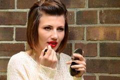 Junge Frau malt ihre Lippen Stockbild