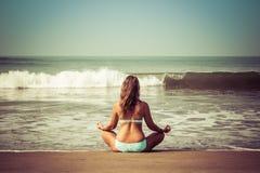 Junge Frau meditiert, sitzend auf dem Ozean lizenzfreies stockbild