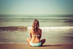 Junge Frau meditiert, sitzend auf dem Ozean stockfoto