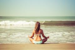 Junge Frau meditiert, sitzend auf dem Ozean stockfotografie