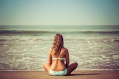 Junge Frau meditiert, sitzend auf dem Ozean lizenzfreie stockfotos
