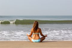 Junge Frau meditiert, sitzend auf dem Ozean stockbilder