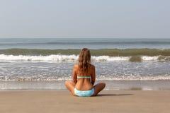 Junge Frau meditiert, sitzend auf dem Ozean stockfotos