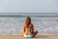 Junge Frau meditiert, sitzend auf dem Ozean stockbild