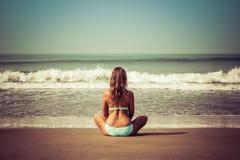 Junge Frau meditiert, sitzend auf dem Ozean lizenzfreie stockbilder