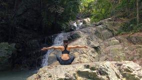 Junge Frau meditiert am Wasserfall stock footage