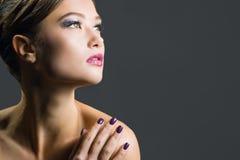 Junge Frau mit Abendmake-up Dunkles Haar und nackten die Schultern, Hand nahe Gesicht halten, schauen weg Stockfotos
