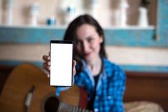 Junge Frau mit Akustikgitarre zeigt Hand mit Smartphone mit Kopienraum, Spott oben das blogging Konzept Lizenzfreies Stockbild