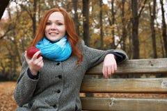 Junge Frau mit Apfel im Herbstpark, in den Gelbblättern und in den Bäumen lizenzfreie stockfotografie