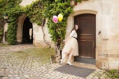 Junge Frau mit Ballonen öffnet Tür Stockbild