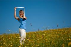 Junge Frau mit Bilderrahmen in der Landschaft im Frühjahr Stockbilder