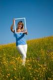 Junge Frau mit Bilderrahmen in der Landschaft im Frühjahr Lizenzfreie Stockfotos