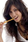 Junge Frau mit Bleistift in ihrem Mund Lizenzfreie Stockfotos