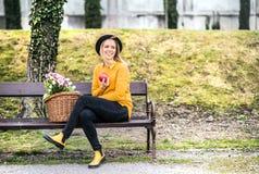 Junge Frau mit Blumen in einem Korb in der sonnigen Frühlingsstadt stockfotografie