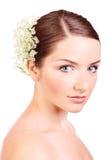 Junge Frau mit Blumen in ihrem Haar Stockfotografie