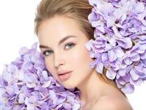 Junge Frau mit Blumenstrauß der Blumen Lizenzfreie Stockbilder