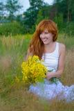 Junge Frau mit Blumenstrauß der wilden Blumen Stockfotos