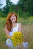 Junge Frau mit Blumenstrauß der wilden Blumen Stockfoto