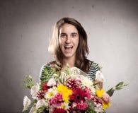 Junge Frau mit Blumenstrauß von Blumen stockbild