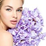 Junge Frau mit Blumenstrauß von Blumen nähern sich Gesicht Lizenzfreies Stockfoto