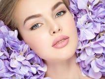 Junge Frau mit Blumenstrauß von Blumen nähern sich Gesicht Lizenzfreie Stockfotos