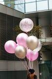 Junge Frau mit bunten Ballonen gegen Glasfassadengebäude stockfotos