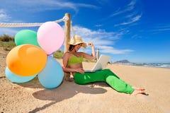 Junge Frau mit bunten Ballonen unter Verwendung des Laptops Lizenzfreies Stockbild