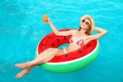 Junge Frau mit Cocktail im Pool stockfoto