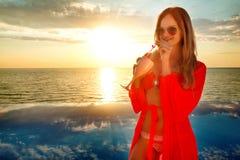 Junge Frau mit coctail im Sommerkleid, das auf einem Pool- und Seehintergrund steht Sonnenuntergang stockfotos
