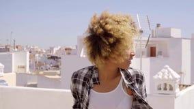 Junge Frau mit dem Afro, der auf städtischer Dachspitze sich entspannt stock video