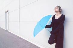 Junge Frau mit dem blauen Regenschirm, der auf den Regen wartet Lizenzfreie Stockbilder