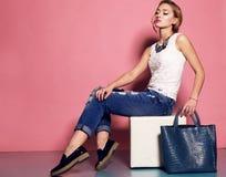 Junge Frau mit dem blonden gelockten Haar trägt elegante Bluse und die Jeans und hält eine große Tasche Lizenzfreies Stockbild