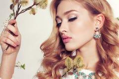 Junge Frau mit dem blonden gelockten Haar trägt elegantes Spitzekleid und -Juwel Stockfotografie